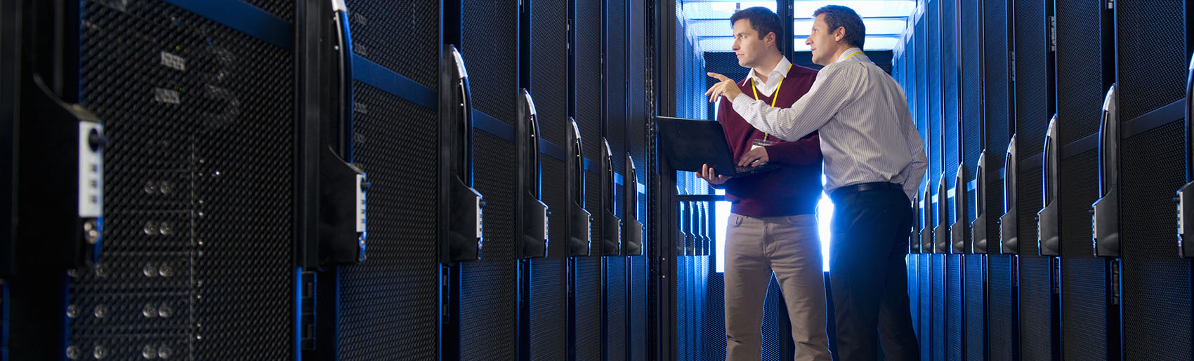 Two people standing near computer servers
